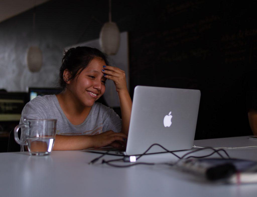 Una joven sonriendo frente a la pantalla de la computadora.